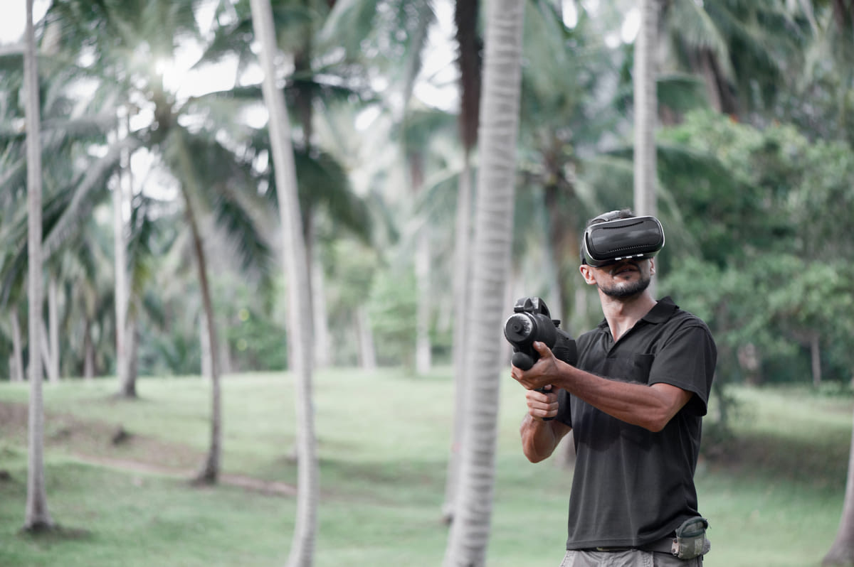 Canva - Man in virtual reality headset playing video game outdoors
